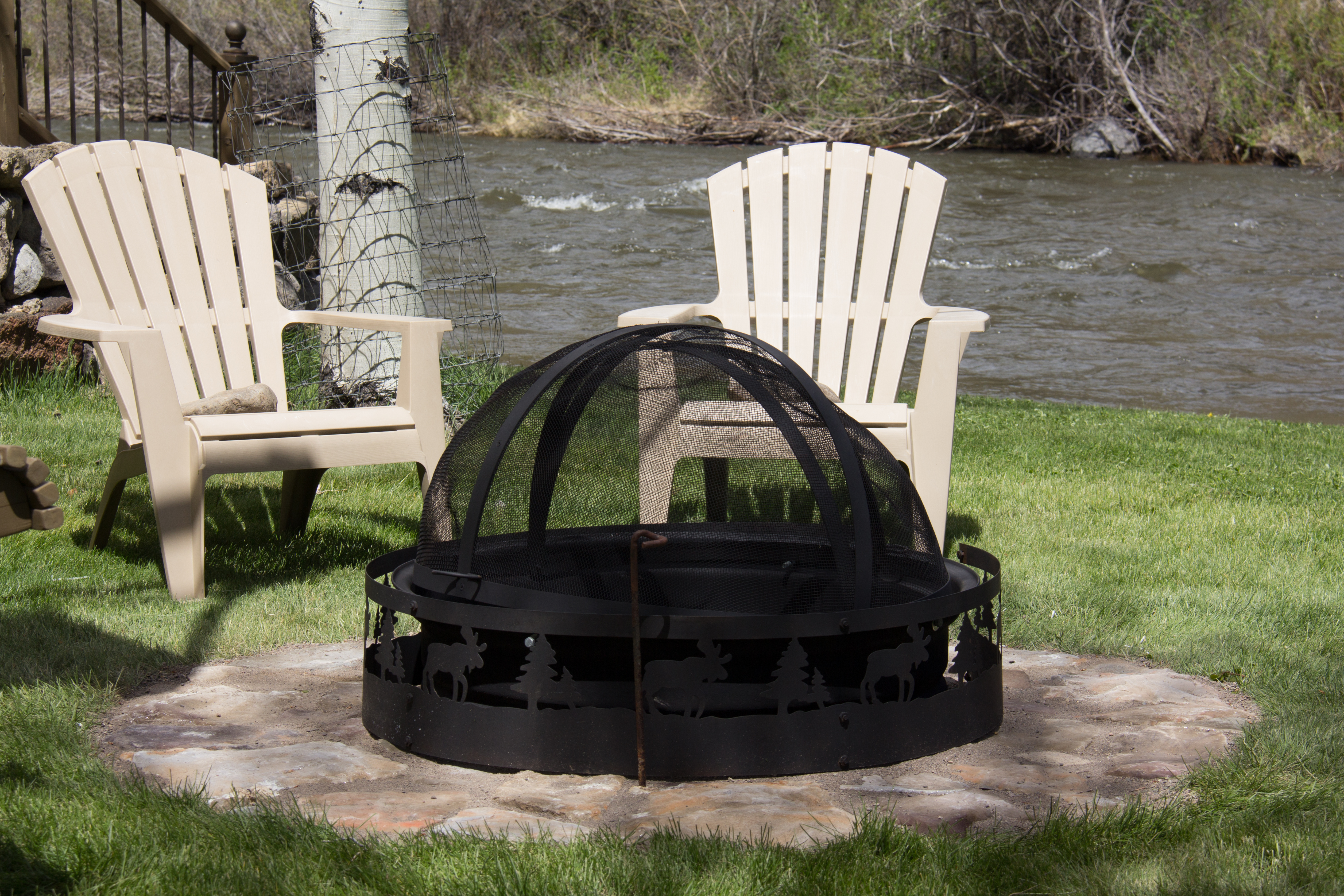 two adirondak chairs by a stone fire pit by the river