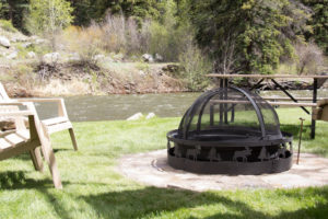 stone fire pit with a picnic table by the river