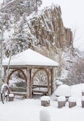 snow covered cliffs  and brown wooden arbor on the banks of the river