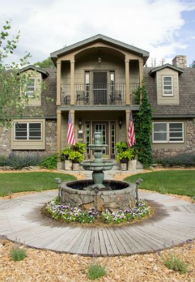 Summer view of front of inn with wooden walkway and front entrance water fountain