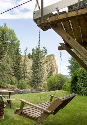 Hanging porch swing overlooking summer time view of private cliffs and river
