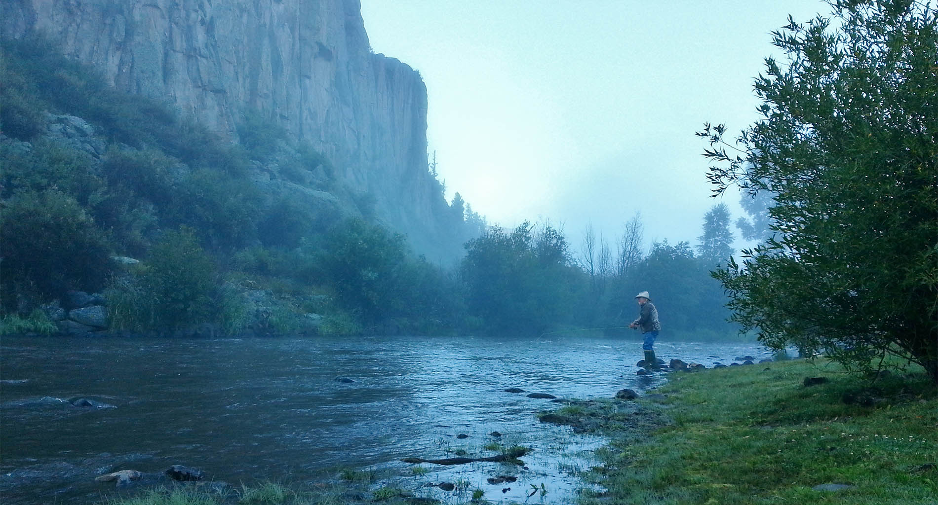 Man fishing in river with green trees and grass, tall cliffs, foggy atmosphere
