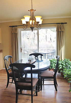 A dark brown diningroom table with four chairs sits in the center of a brightly lit room