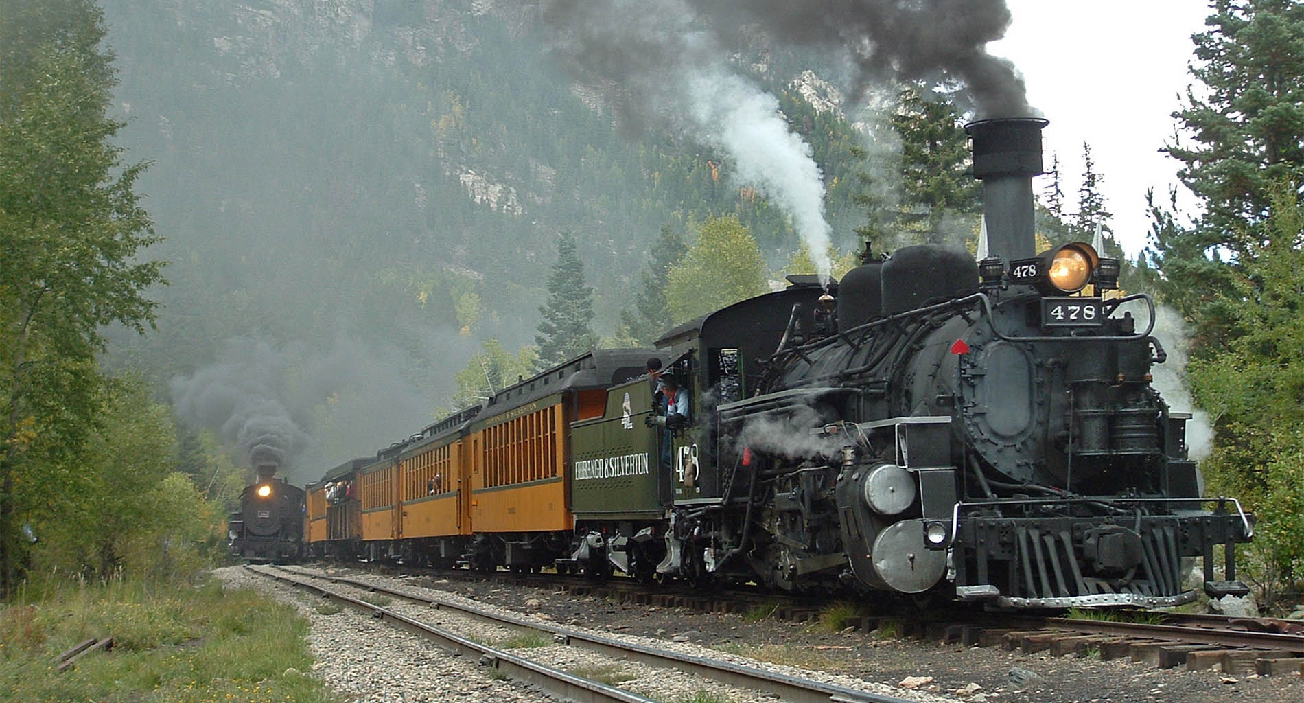Two old locomotives with black smoke on train tracks with green forest and mountains in background
