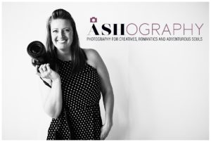 black and white photo of photographer Ashlee Bratton holding a camera in front of a white background