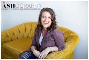 photographer Ashlee Bratton laughing while sitting on a yellow couch