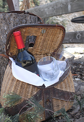 A tan and brown picnic basket with a bottle of wine and two glasses sits on the ground