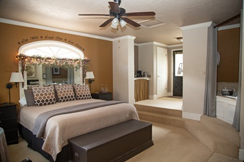 honeymoon suite with king bed featuring grey toned bedding and jacuzzi tub