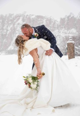 winter bride and groom in a dip kiss by the cliffs