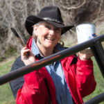 A smiling woman in a red coat and black cowboy hat holds a paintbrush and container of paint