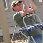 A man in a green shirt and tan hat is helping build a greenhouse