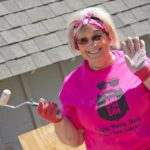 A smiling woman in a pink shirts waves with one hand while holding a paint roller in the other