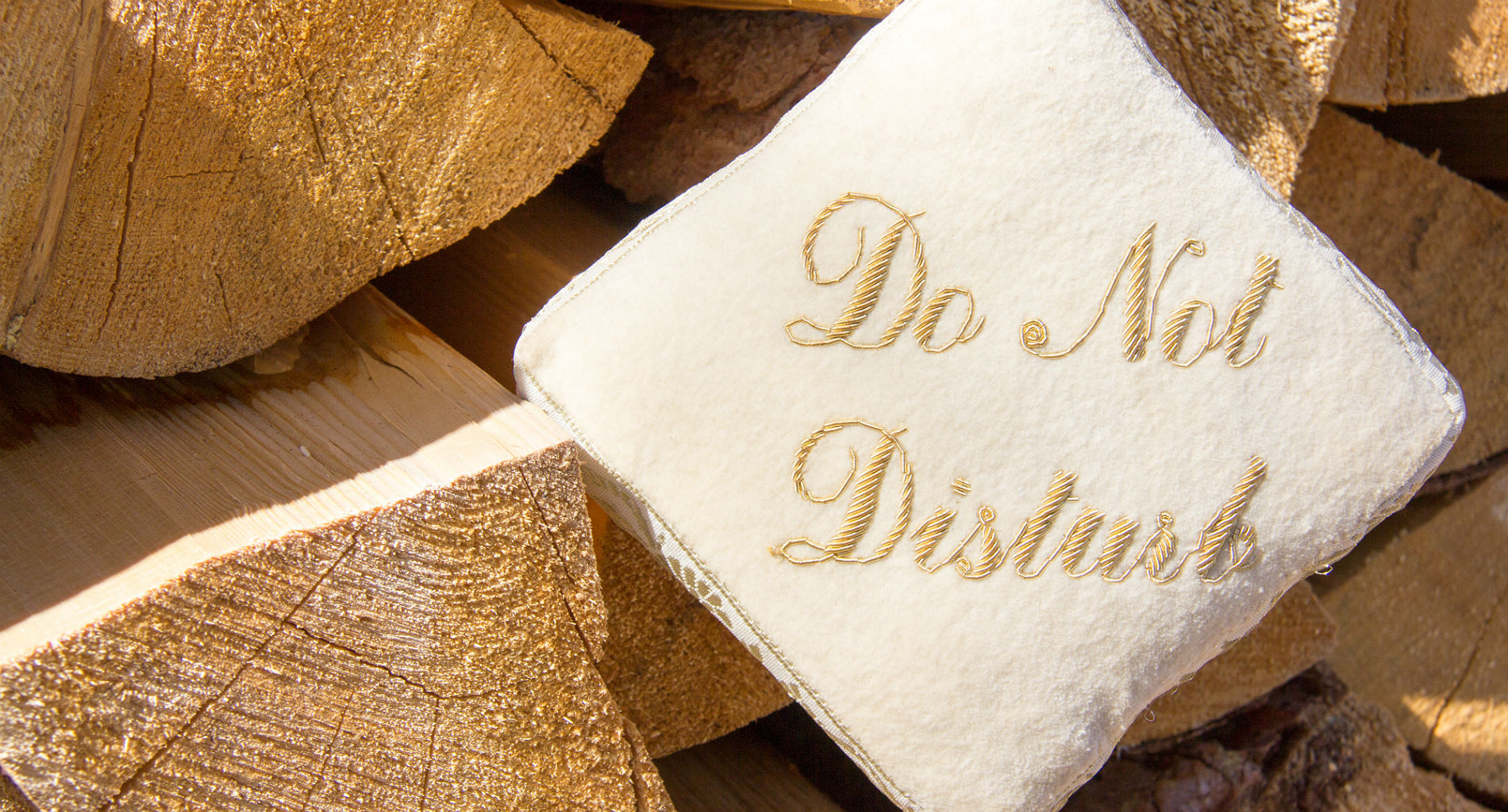 "A small white pillow with gold lettering reading ""Do Not DIsturb"" sits among a pile of freshly cut wood"