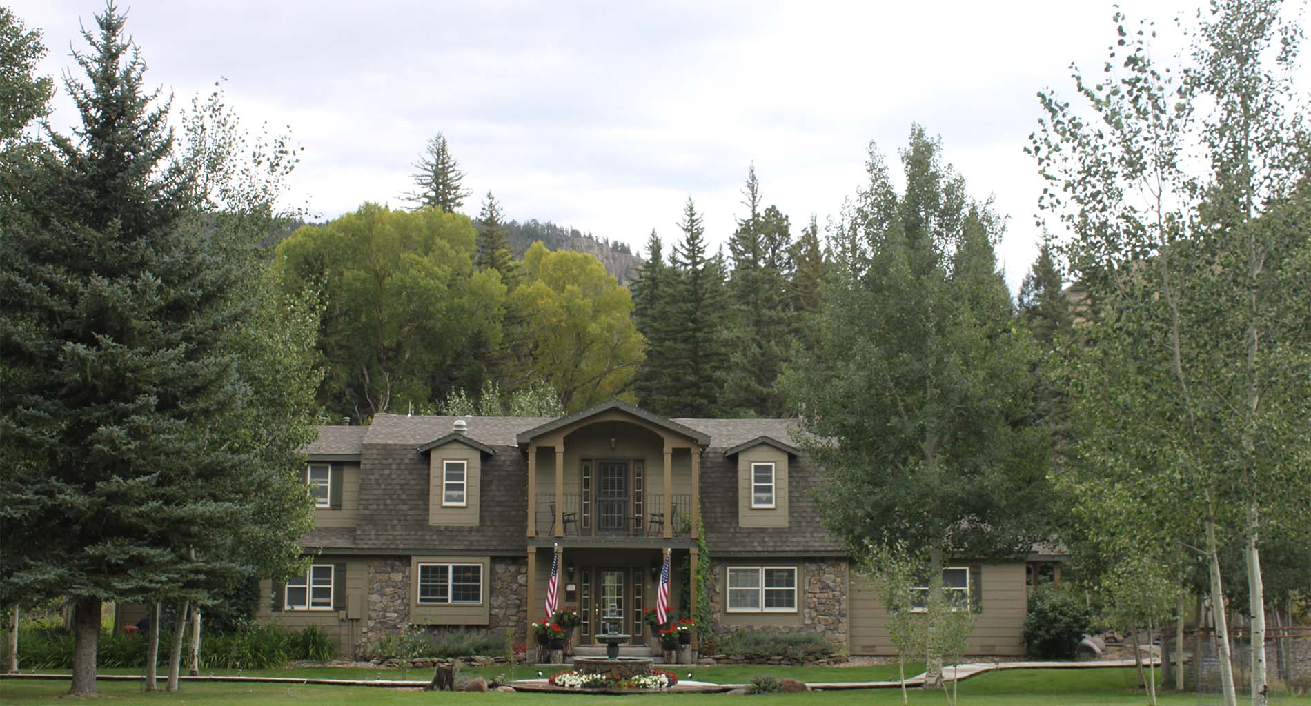 Front exterior of inn with green grass and trees, red and white flowers and two American flags