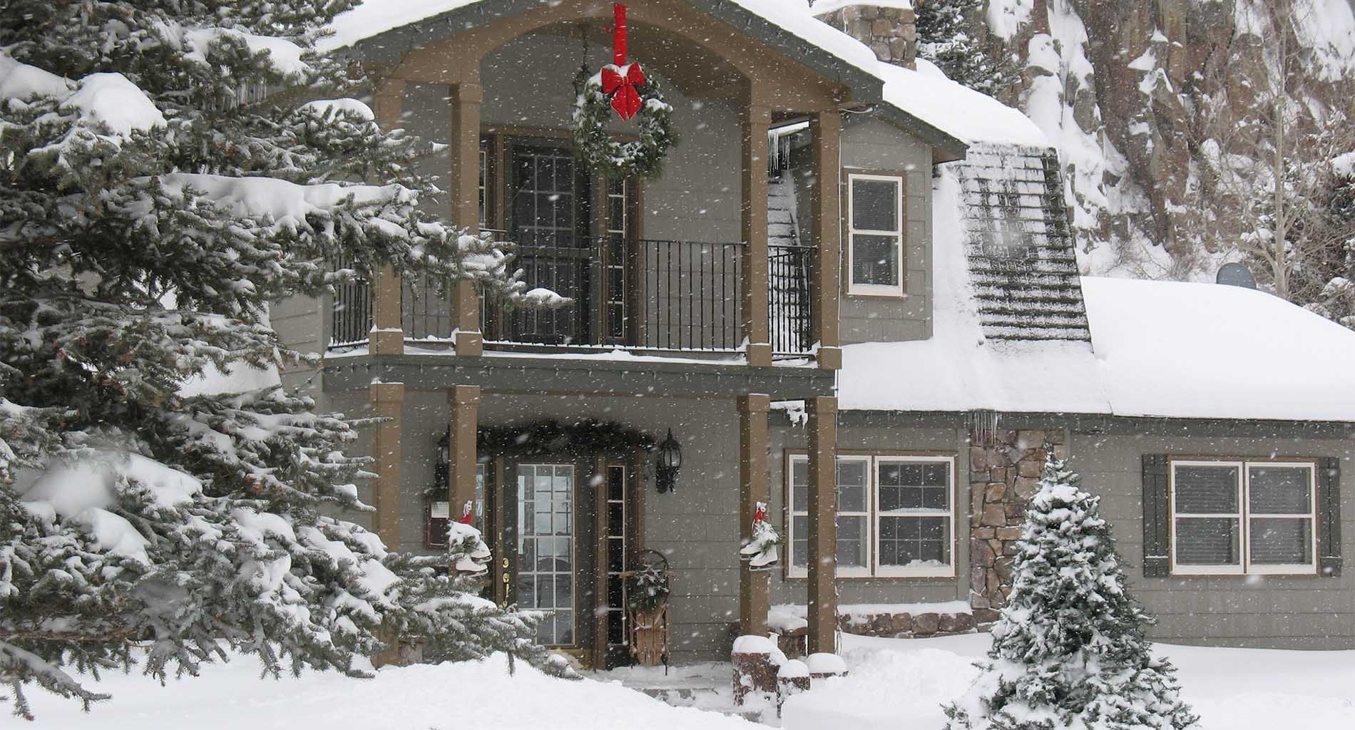 Front exterior of inn with snow drifts and falling snow, white ice skates, large Christmas wreath with big, red bow