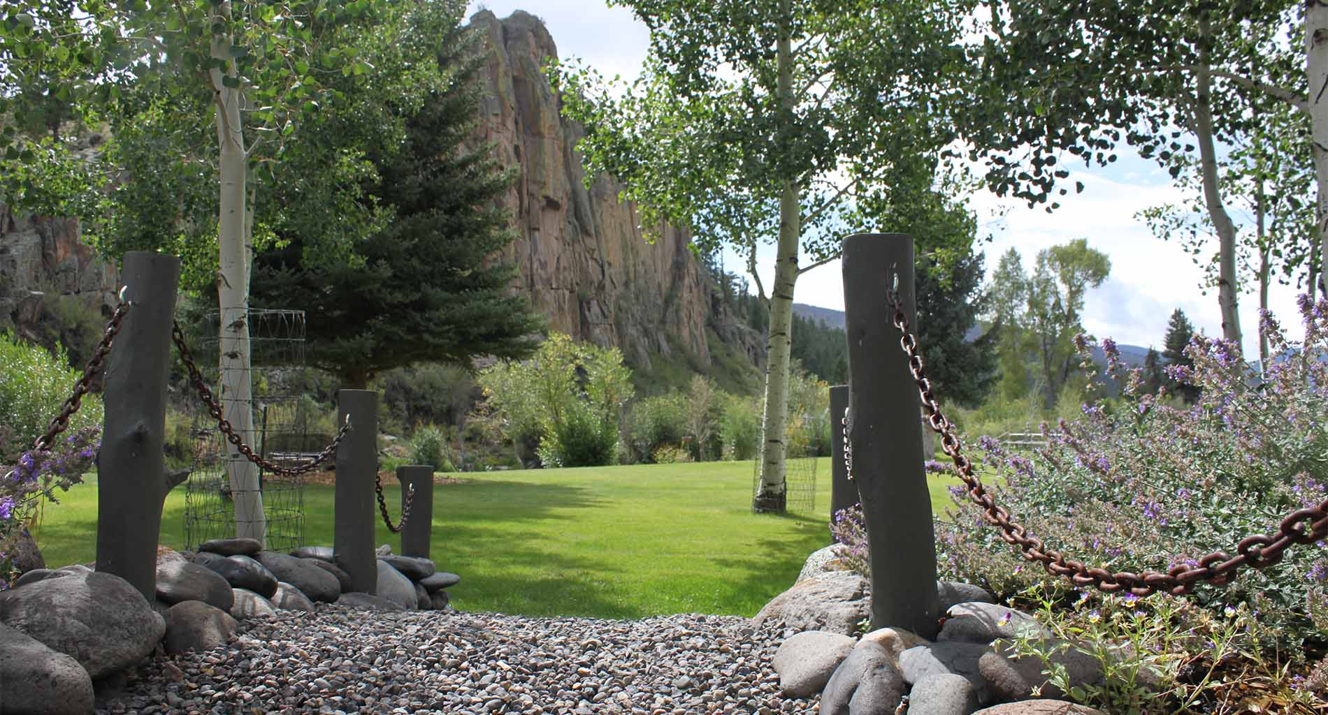Back yard of inn with tall cliffs, green grass, aspen trees, purple flowers, and gravel pathway