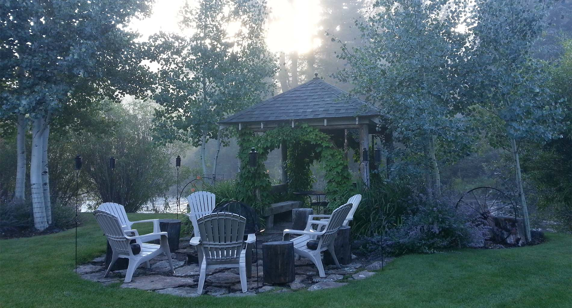 Log arbor, green vines, purple flowers and Adirondack chairs around a fire pit in an early morning, foggy atmosphere
