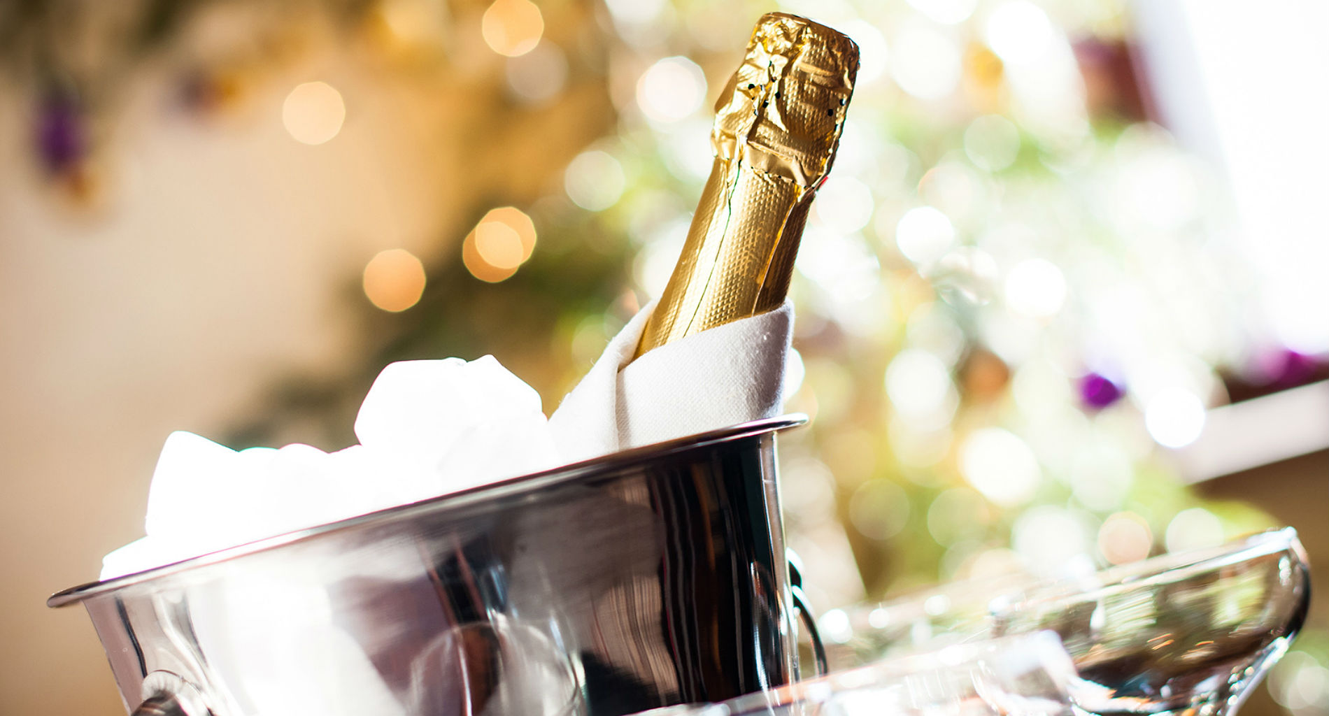 An unopened bottle of champagne wrapped in a white cloth rests in a shiny silver bucket